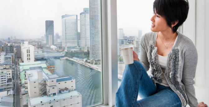 A woman admires the view from a hotel room.