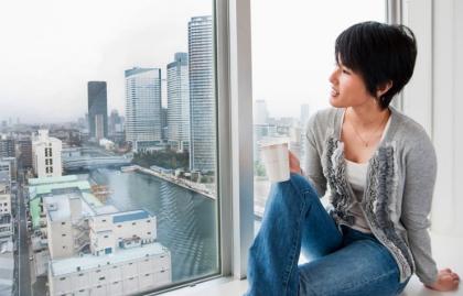 Una mujer admira la vista desde una habitación de hotel - Consejos de Samantha Brown sobre las primeras cosas que hace al viajar a algún lugar