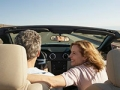 Couple in convertible car. Weekend Getaways.