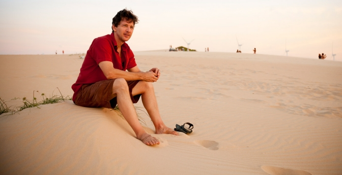 Author Andrew McCarthy sitting on a beach