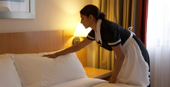 Chamber maid working in hotel bedroom.