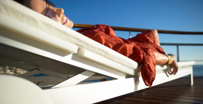woman relaxing on chaise on cruise ship