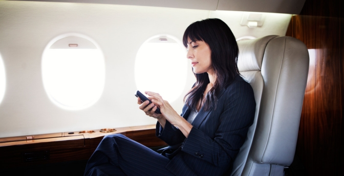 Woman on plane using smartphone