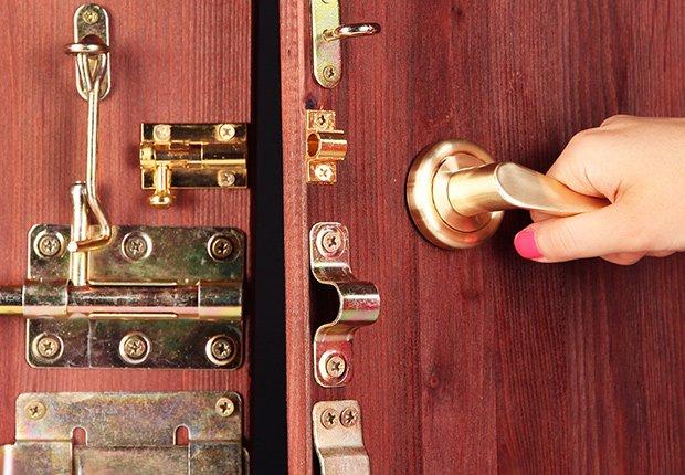 Claves para mantener tu casa segura cuando estás lejos - Persona cierra con seguro una puerta