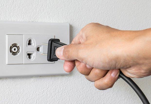 Claves para mantener tu casa segura cuando estás lejos - Mano desconectando un electrodoméstico