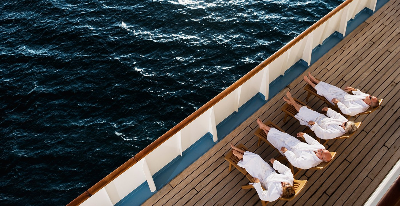 Four friends in white robes relaxing on the deck of a cruise ship