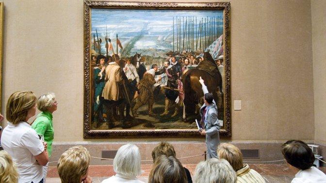 Tour guide and tourists looking at La Rendicion de Breda by Velazquez in the Museo del Prado, Madrid, Spain