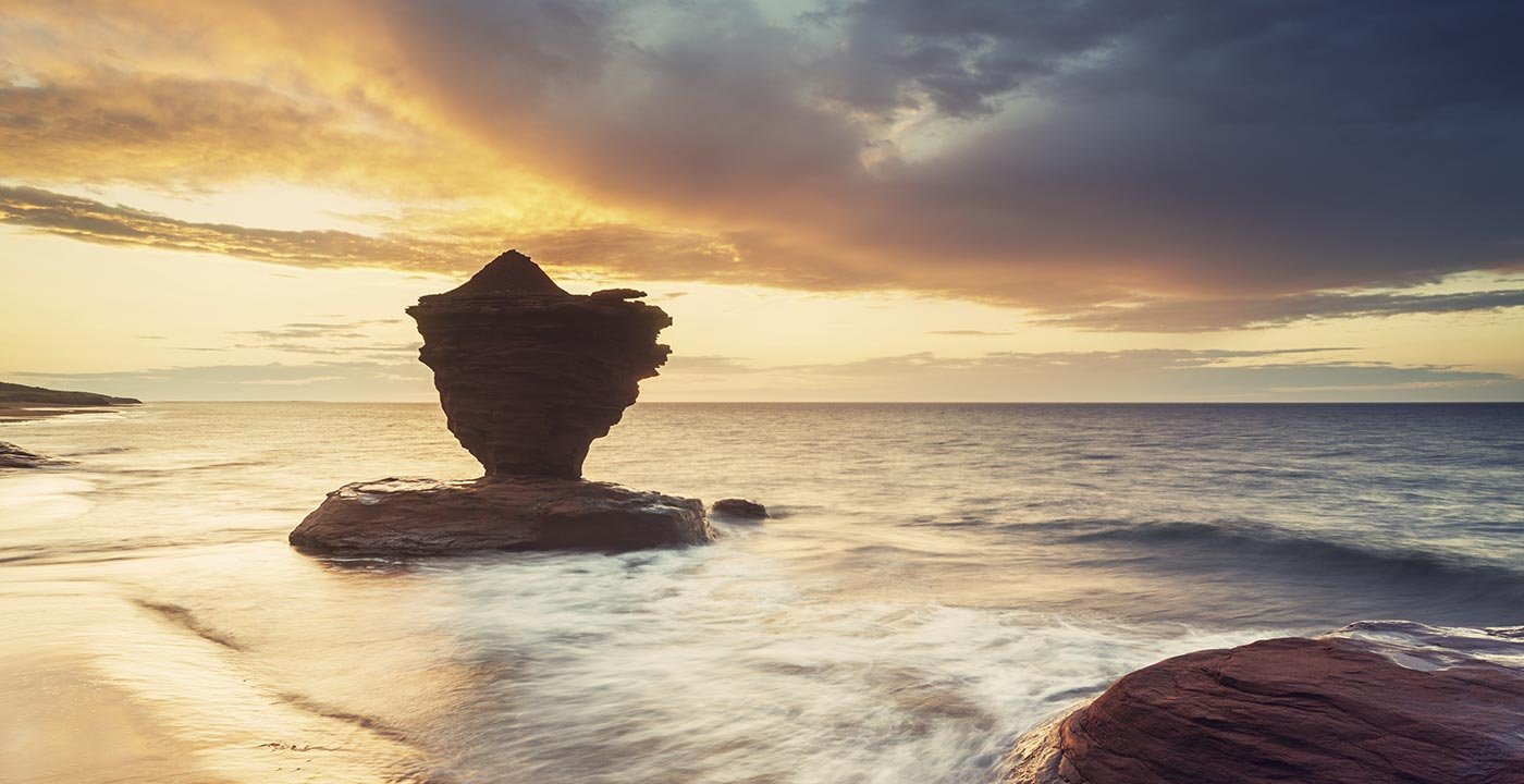 A striking rock formation known locally as the 'Teacup' silhouetted against a dramatic sunset on Prince Edward Island's North coast